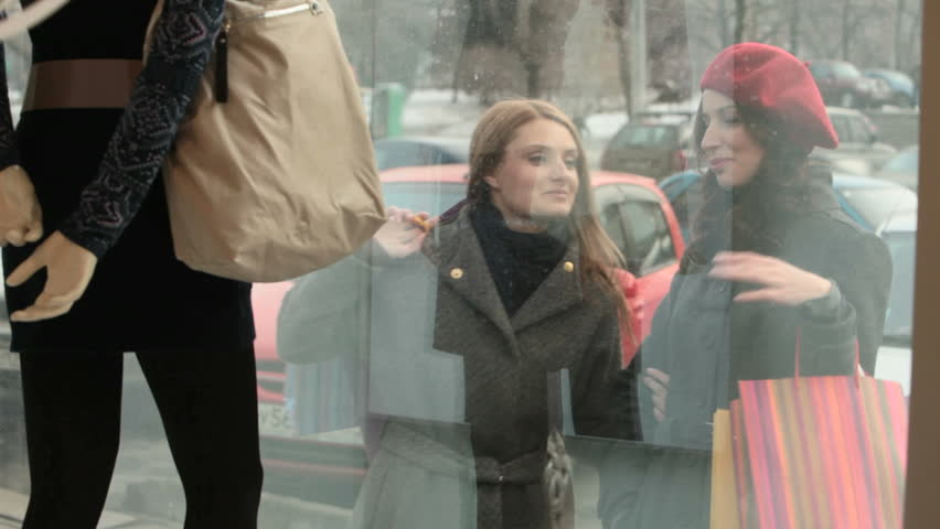 Two girls with shopping bags looking at the shopping window and discussing the outfit