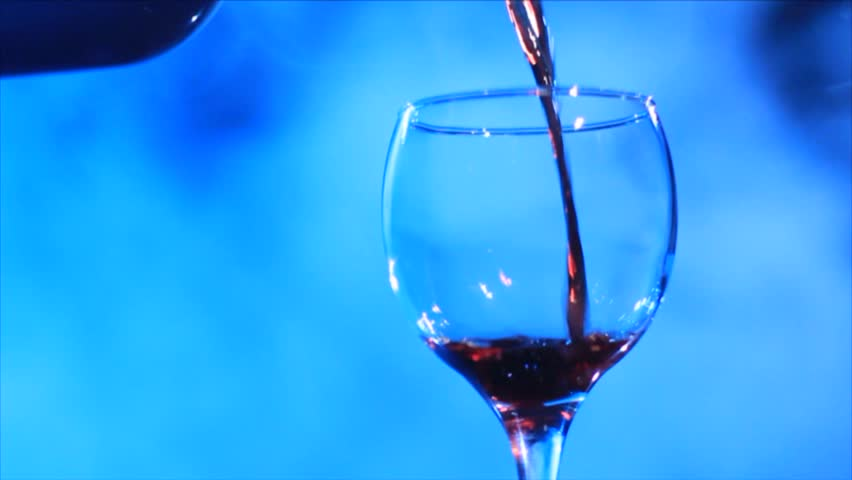 Pouring wine into a glass and smoke on the red background
