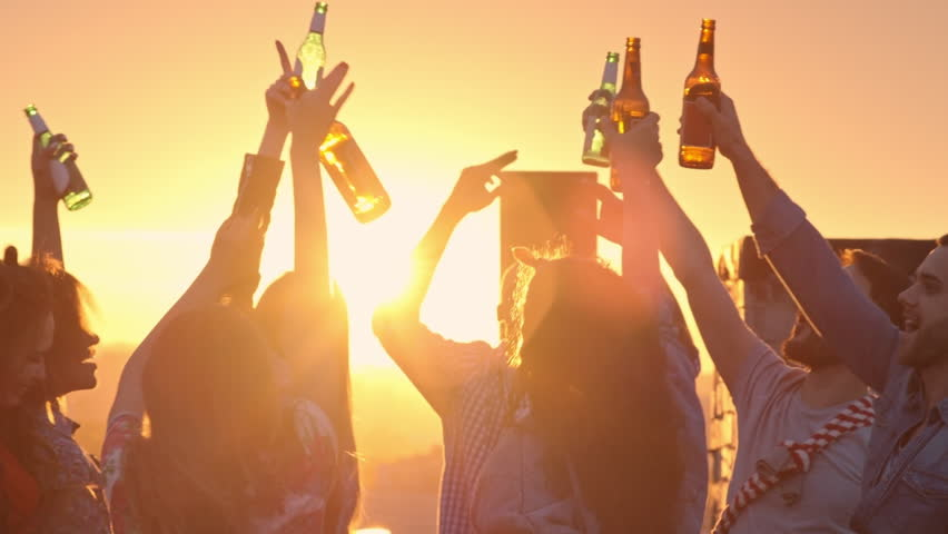 Group of multi-ethnic young people toasting with beer bottles and dancing to the music played by dj at urban rooftop party at sunset