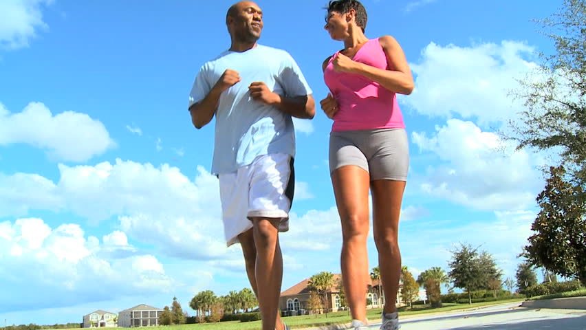 Young ethnic couple keeping to a fitness program together jogging outdoors
