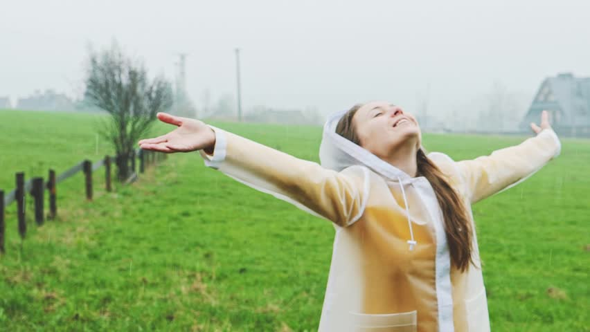 Happy Woman Enjoying the Rain. SLOW MOTION 120 fps. Girl Smiling and Dancing under the Pouring Rain in a transparent Raincoat. Autumn or Spring changing Weather.