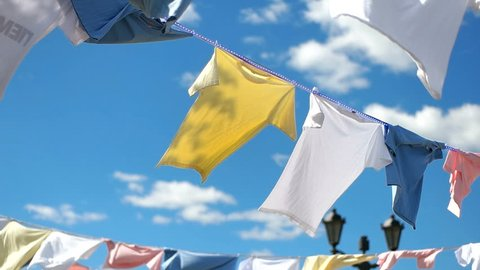 A lot of t-shirts are dried in the Sun rope slow motion