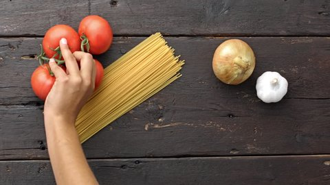 4k Time lapse of woman hands placing ingredients of a recipe of vegetarian pasta on kitchen counter table.