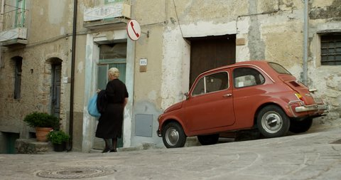 Old women in black passing a red Fiat in old town of Badolato, Calabria, Italy.