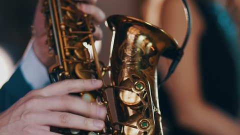 Saxophonist in dinner jacket play on golden saxophone. Live performance. Jazz music.