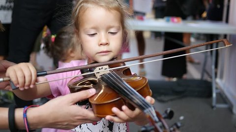SOFIA, BULGARIA - AUG 28, 2016: Free public cultural urban festival in pedestrian city center. Child little girl try play violin - music instrument educative demonstration