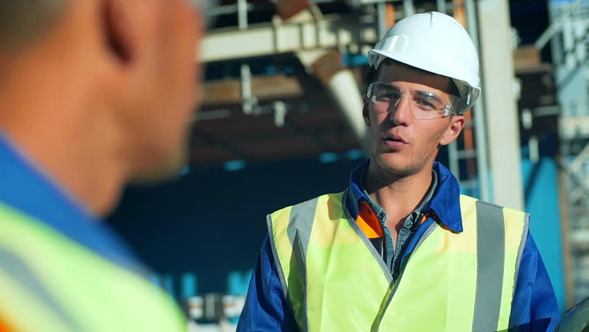 Industrial engineer and worker discussing in factory. Close-up