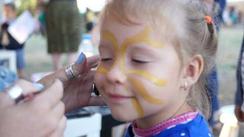 Painting body art on a face of little cute child girl - happy childhood portrait
