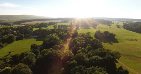 Aerial view of a beautiful countryside scene at sunset towards the coastline