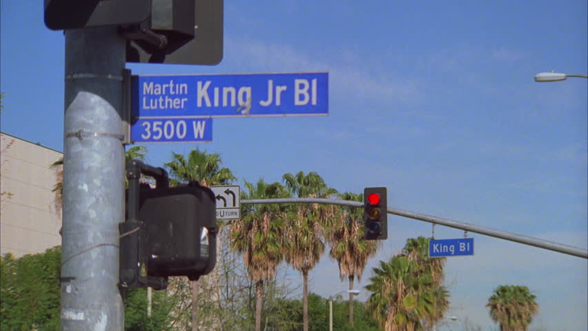 day Street sign foreground , Martin Luther King Jr Bl. street sign, traffic signal palm trees background Los Angeles