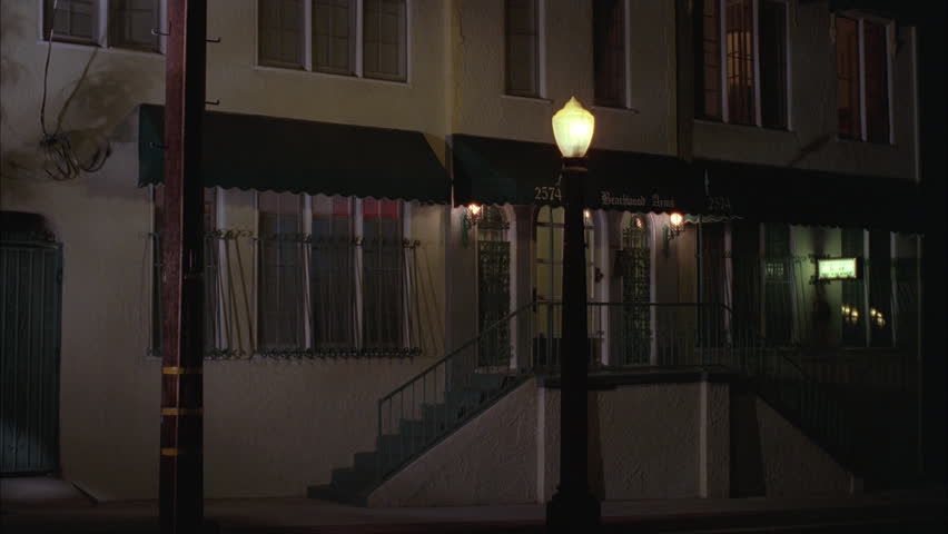 Night Close small two story apartment building steps up green awnings lit street lamp front tilt up upstairs windows, lights Spanish tile roof | Shutterstock HD Video #19232953