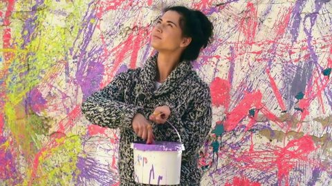 Slow motion of inspired young woman artist splatter painting walls in her house, throwing bright colors from bucket with big brush, standing against colorful wall background