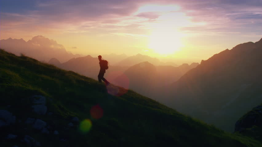 Aerial - Epic shot of a man hiking on the edge of the mountain as a silhouette in colorful sunset (edited version) | Shutterstock HD Video #19249192
