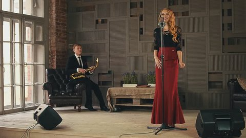 Jazz vocalist perform on stage. Saxophonist stand up and start play. Duet. Music. Live concert. Retro style
