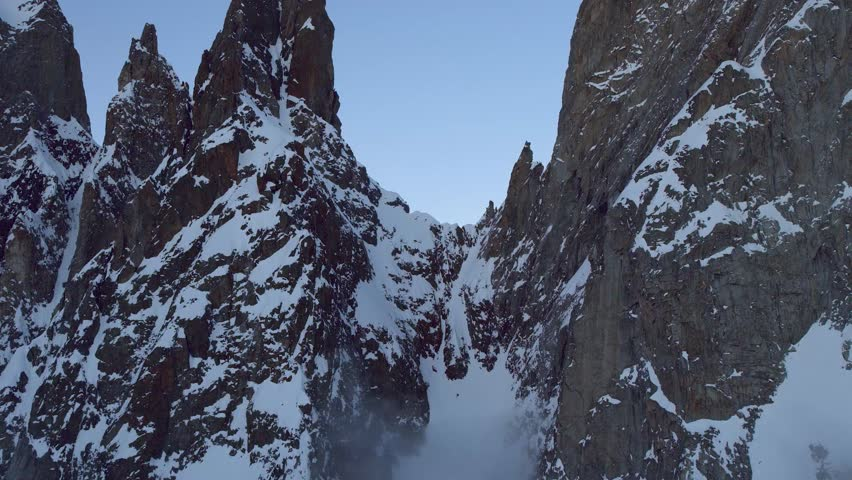 Slow Mo Aerial shot flying through two snowy peaks to next cloudy valley in Courmayeur, Aosta Valley/Italy (Courmayeur, Aosta Valley/Italy - March, 2016)