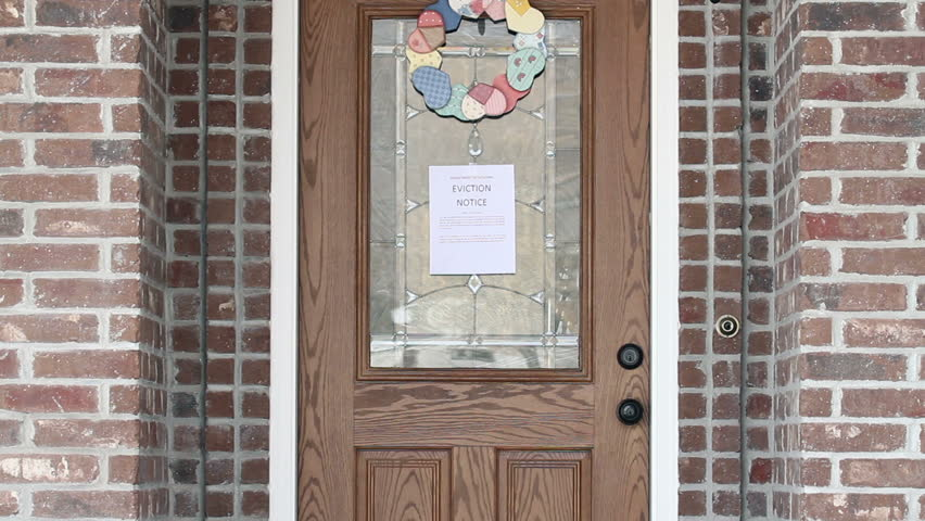 Eviction notice on front door of house as home owner returns.