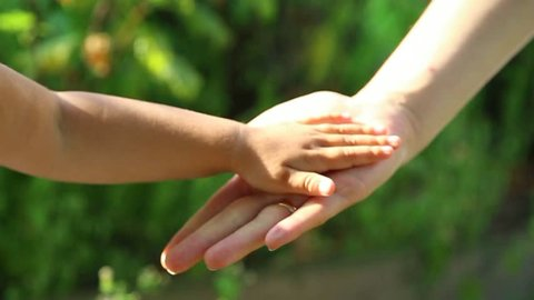 Close up of anonymous little child hands touching hands of her young mother with love. Happy family of mother and daughter having fun outside on summer day. Human hands at on green leaves background.