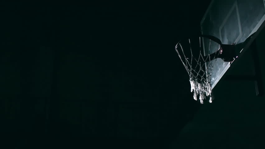 Unrecognizable basketball player in jumping in the air and slamming ball in the rim in slow motion at night