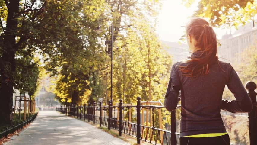 Runner Woman Running in the Sunny City Park Exercising Outdoors. Steadicam STABILIZED shot, SLOW MOTION 240 fps. Sportswoman Listening to Music during Morning Training. Healthy Lifestyle. Lens Flare. | Shutterstock Video #19353142