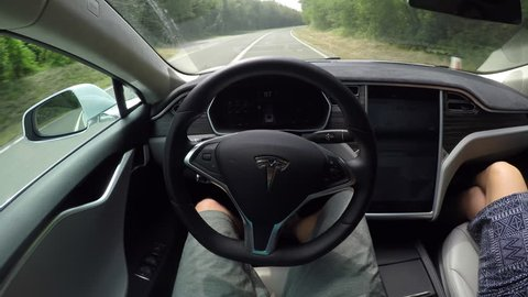 AUTONOMOUS TESLA CAR, JULY 2017:  Self driving Tesla electric car using sensors, navigating winding street through forest without driver. Autonomous car driving fast on meandering road and steering wh