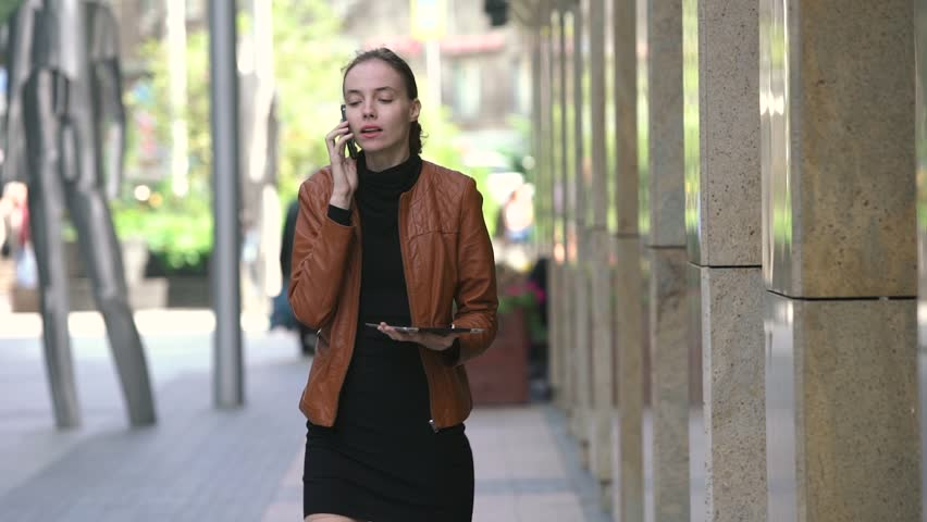 Beautiful young business woman with tablet talking on cellphone on street | Shutterstock HD Video #19366222