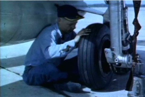 Navy planes' engines, tires, and wings are carefully inspected before the planes go for a test run in 1959. (1950s)