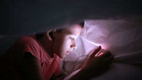 Young boy playing with a cellphone or smartphone on a bed. night