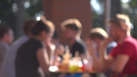 Defocused young people eating fast food outdoor. 4K background bokeh video
