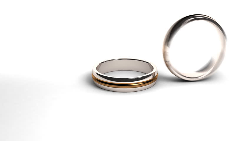 Studio Shot Of Two Wedding Rings Falling Against White Background