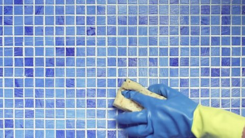 Cleaning swimming pool tile with sponge