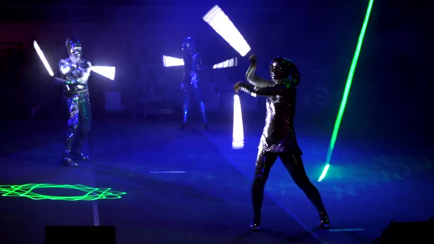 """MOSCOW, RUSSIA - JANUARY 30, 2016: Final of Moscow stage of National Cup of """"Robot wars-2016"""" at VDNH. A few people perform on arena in darkness in strange alien costumes and with lightsabers"""