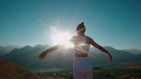 Young cheerful woman raising hands on beautiful mountain top above the Golden sunset sky