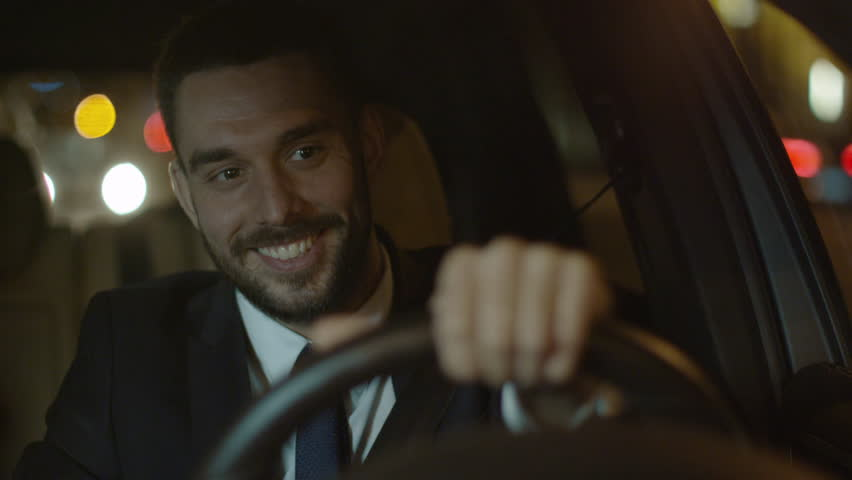 Happy Smiling Businessman Performing Winning Gesture while Driving a Car at Evening. Shot on RED Cinema Camera in 4K (UHD). | Shutterstock HD Video #19484302
