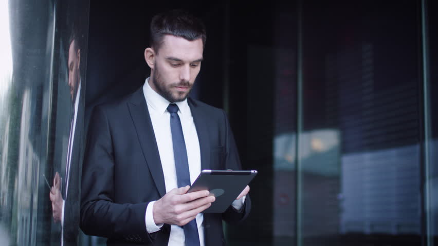 Businessman Using Tablet Computer Outdoors. Shot on RED Cinema Camera in 4K (UHD).
