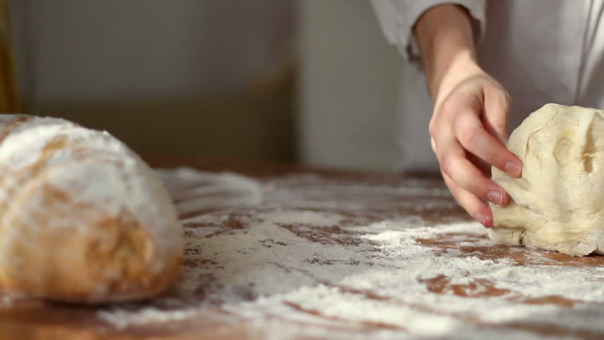 Female hands kneading dough in flour on table, dolly shot