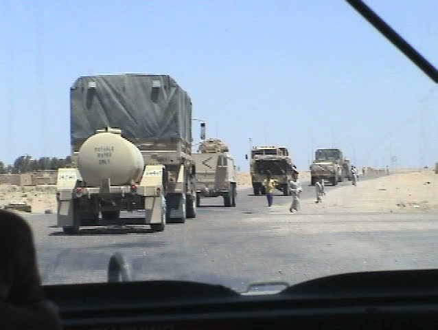 IRAQ - CIRCA 4/30/03: U.S. Soldiers share food and candy with Iraqi children running alongside their convoy.