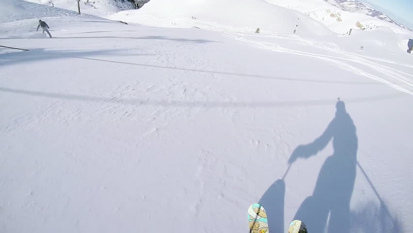 FIRST PERSON VIEW CLOSE UP: Unrecognizable skier riding fresh powder snow down the steep mountain slope, jumping over rocky overhang. Freeride skier skiing in backcountry mountain ski resort