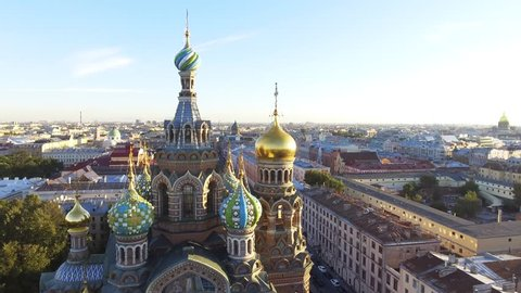 Russia, Saint-Petersburg, 2 September 2016: Aero video filming of the cathedral Church of the Savior on Blood at sunset, gold domes and crosses shine, roofs of St. Petersburg, power, a panorama,