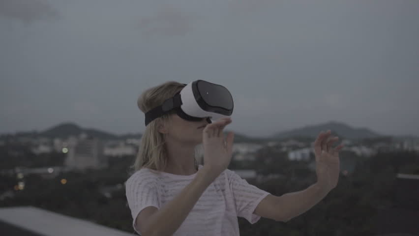 Woman having fun with virtual reality glasses while standing on the roof during early evening - 360 video in slow motion