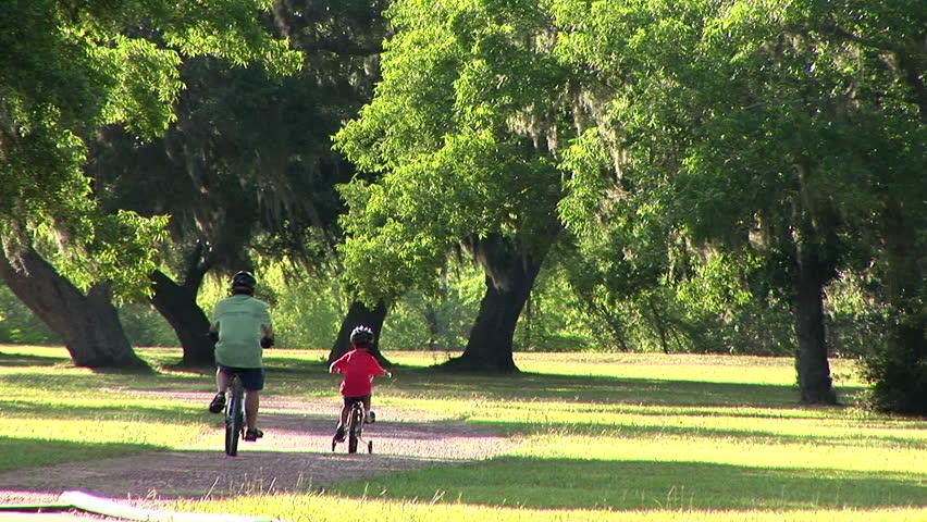 father and son riding their bikes through a park