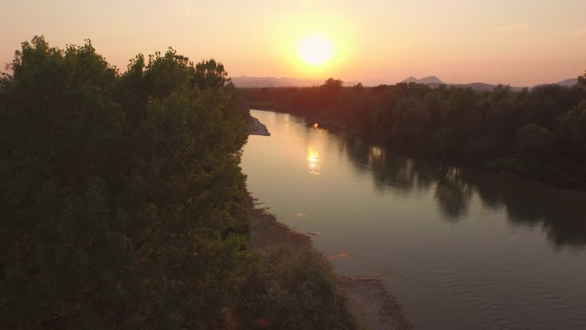 AERIAL: Flying above quiet wide river, lush riverside bushes, tall trees and rocky riverbank at magical golden sunset. Beautiful high overgrown hills covered in mist in the background at sunrise | Shutterstock HD Video #19583212