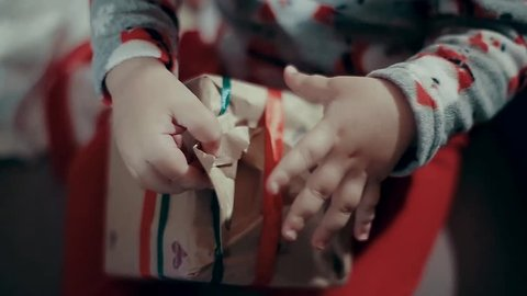 Little Children Hands Trying to Open a Gift, Wrapped With Paper. Displays of Paper, Closes and Turns the Box.