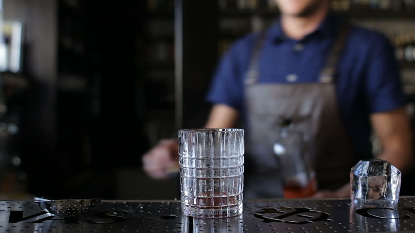 The bartender puts a whiskey in a cocktail | Shutterstock HD Video #19607542