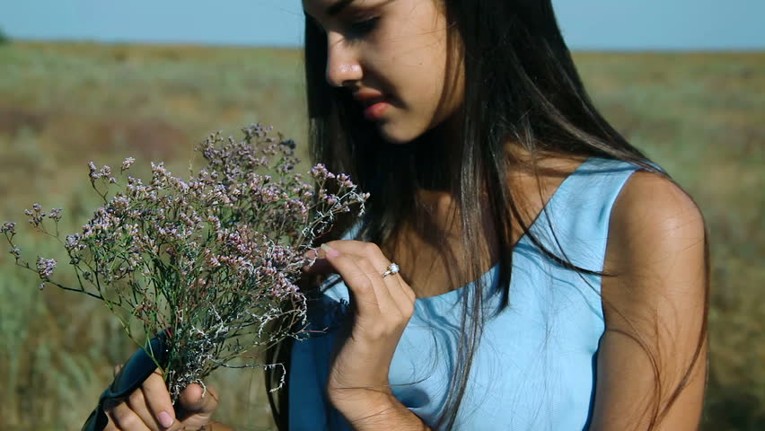 Young Beautiful Girl In A Blue Dress Enjoys Flowers Steppe. A Young Woman In A Meadow. Steppe. Blossoming Sunny Meadow W