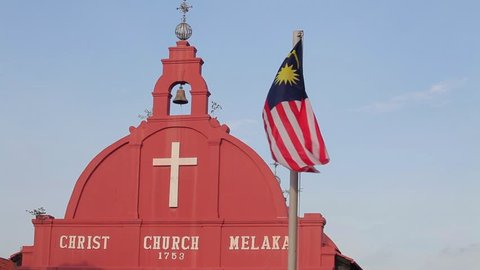 Waving Malaysia flag in front of Christ Church, an 18th-century Anglican church in the city of Melaka, Malaysia. It is also the oldest functioning Protestant church in Malaysia.