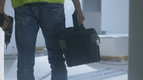 Construction Worker Walking inside Building Under Construction and Carrying Toolbox. Shot on RED Cinema Camera in 4K (UHD).