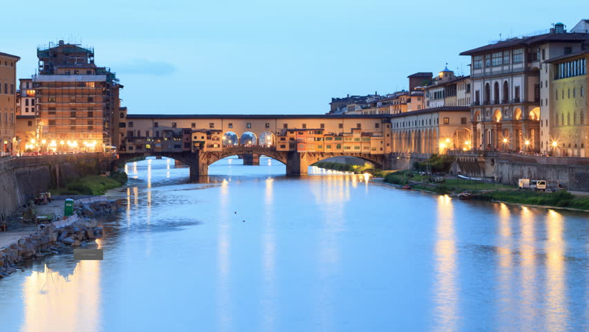 "Time lapse of sunset on Ponte Vecchio in Florence, with street lamps light reflections in the water. The ""Old Bridge"" is a Medieval bridge over the Arno River in Florence, Tuscany - Italy"