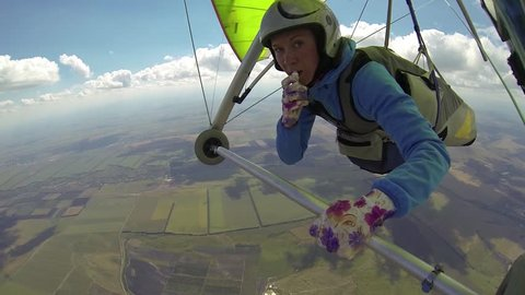 Young woman doing make-up in flight on a hang glider. She piloted the glider and pulls out lipstick and paints her lips