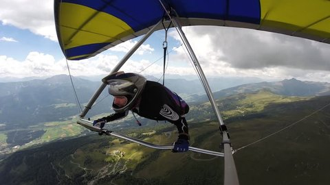 Man flying on a colorful hangglider. Beautiful colorful hang glider quietly flies straight. Shooting with on-board GoPro camera.