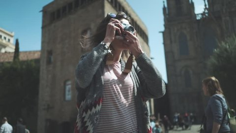 Portrait shot of young hipster traveler girl walking in the city and take picture via vintage camera outside, attractive woman traveling at Europe looking landmarks in Barcelona, slow motion